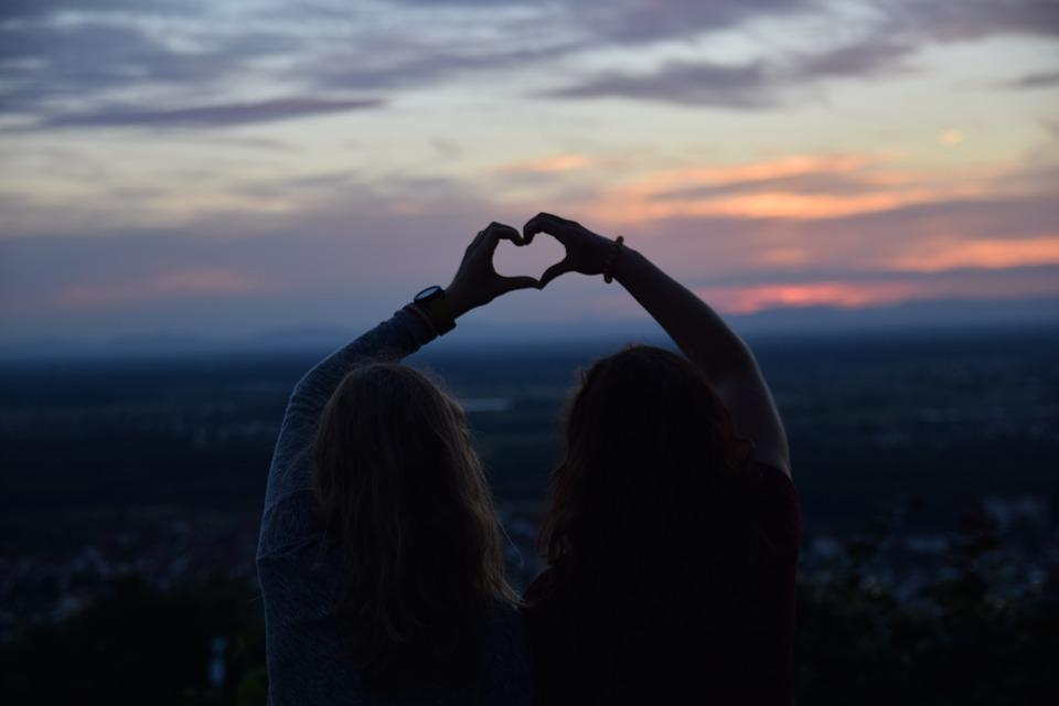 zwiazkimilosci.pl: przyjaciółki pokazują serce dlonią podczas zachodu słońca
