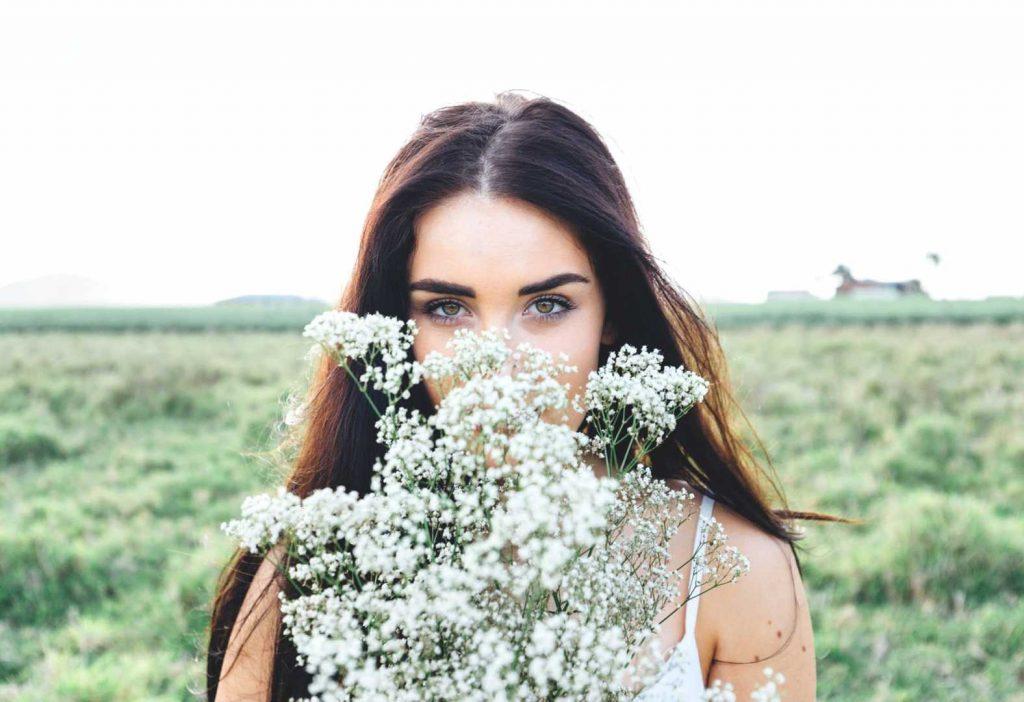 zwiazkimilosci.pl: piękna kobieta wącha białe kwiaty na łące
