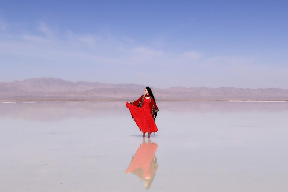 zwiazkimilosci.pl: kobieta w czerwonej sukni stoi w wodzie, piękny widok