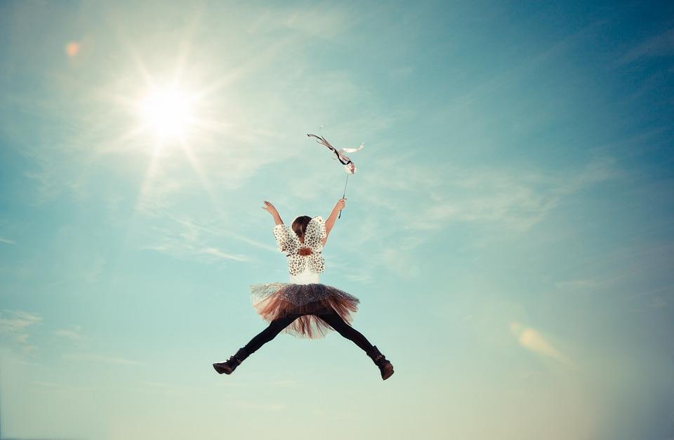 zwiazkimilosci.pl: dziewczynka w sukience skacze ku niebu, słoneczne niebo