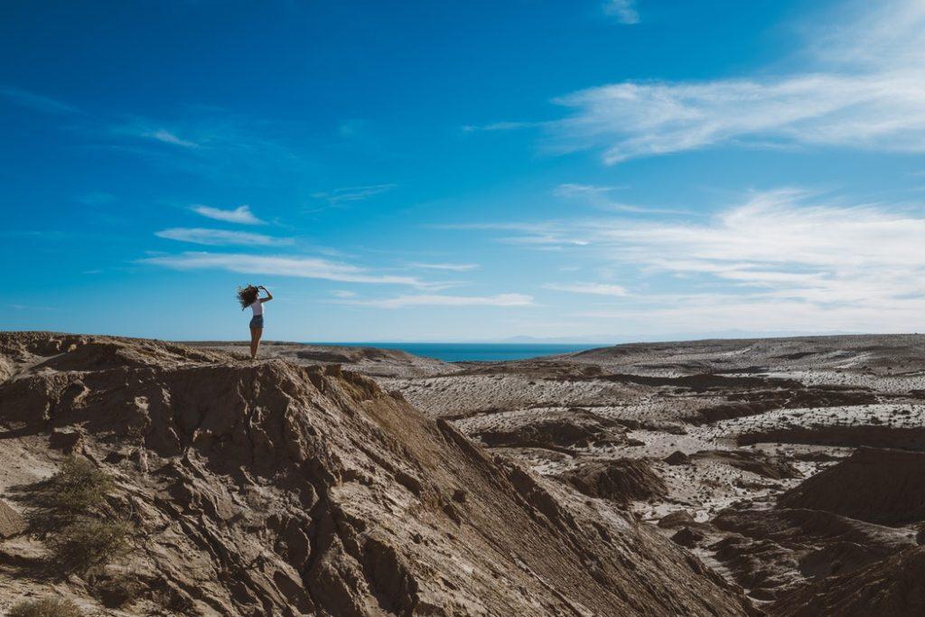 zwiazkimilosci.pl: kobieta patrząca w dal stoi na skale, piękny widok niebo
