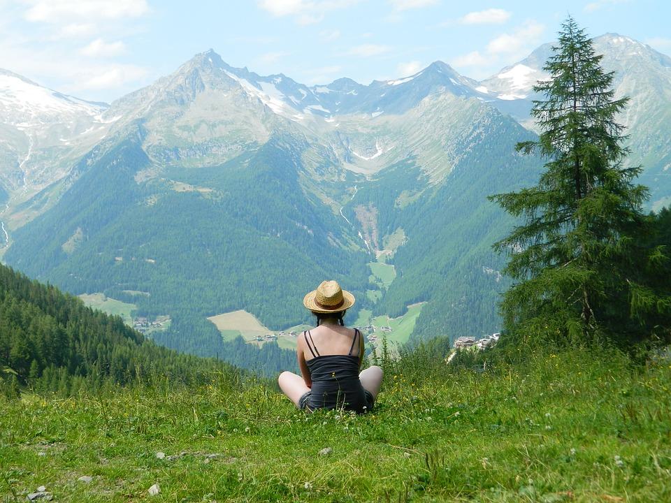 zwiazkimilosci.pl: dziewczyna w kapeluszu siedzi na trawie ogląda górskie widoki