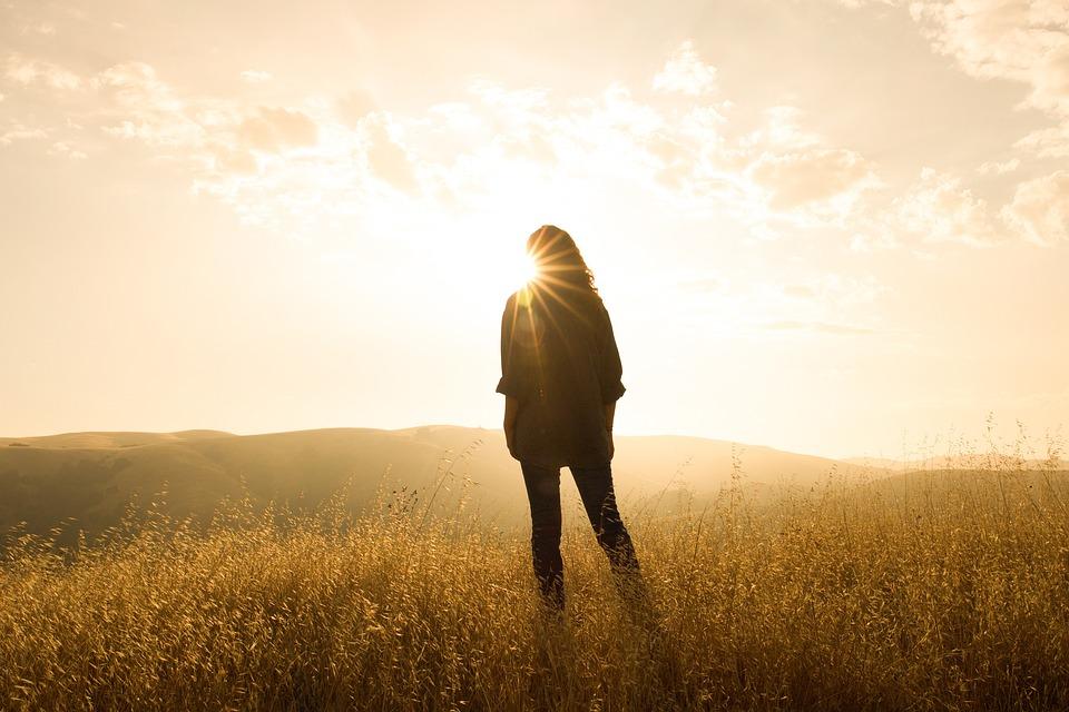 zwiazkimilosci.pl: dziewczyna stojąca na łące w promieniach słońca