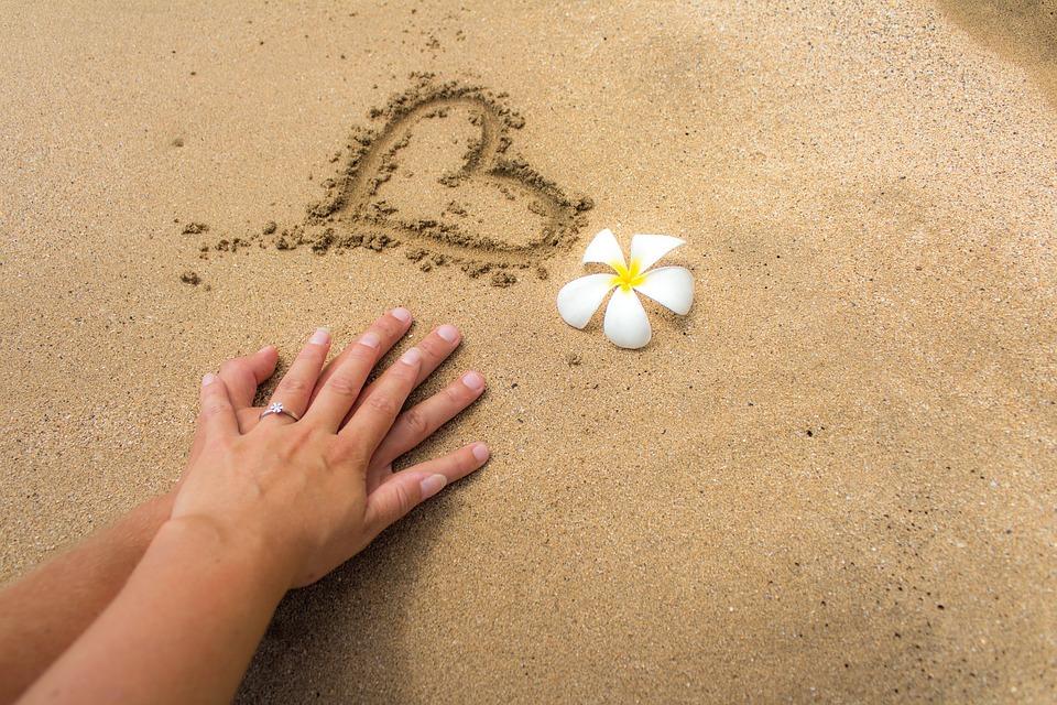 zwiazkimilosci.pl: serce narysowane na plaży biały kwiat i ręce kobiety